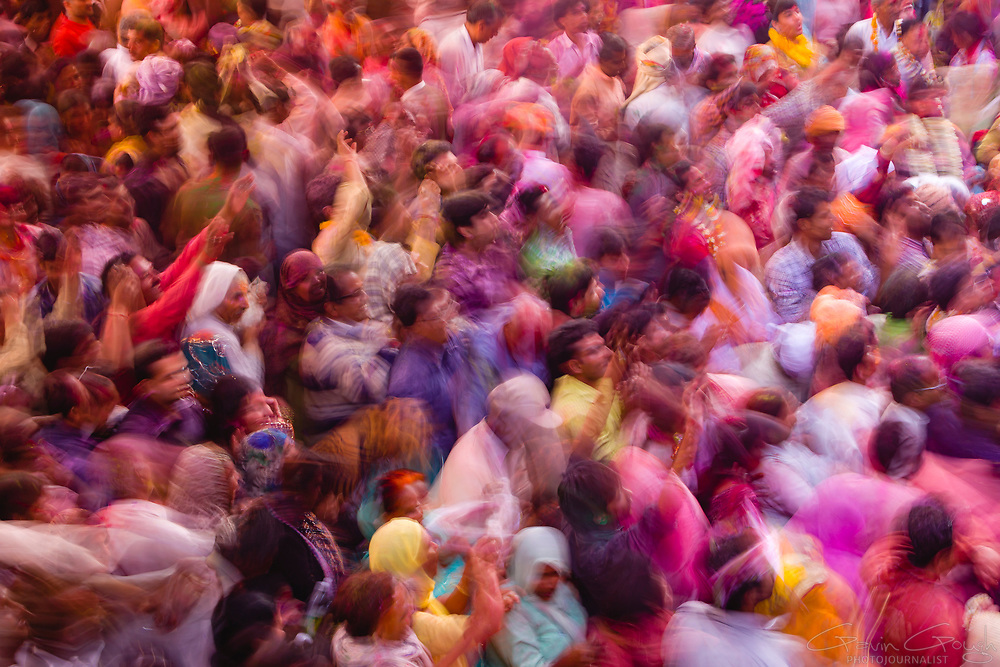 A crowd dancing during Hindu Holi festival celebrations inside the temple, Radha Rani Temple, Barsana, India