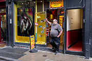 A large man stands in the entrance of an Adult Shop whose window features his exact opposite - a muscular male in Soho, on 8th July 2021, in London, England.