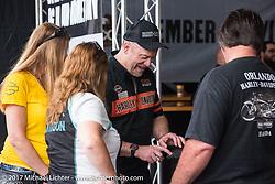 HOG regional rep Bruce Motta gets visitors their free Daytona pins at the Pin-Stop booth at the Harley-Davidson display at the Daytona Speedway during Daytona Bike Week. Daytona Beach, FL. USA. Monday March 13, 2017. Photography ©2017 Michael Lichter.