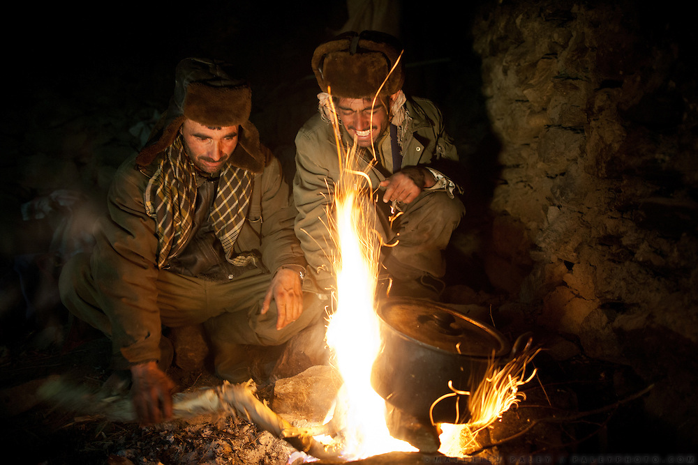 """Cooking diner over a fire in a shepherd place named Zang Kuk (""""Sulphurus spring"""" in Wakhi)...Trekking up the Wakhan frozen river, the only way up to reach the high altitude Little Pamir plateau, home of the Afghan Kyrgyz community."""