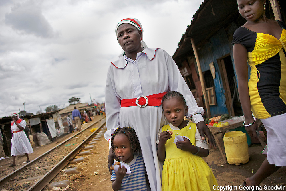 A mother walks with her 2 daughters in their sunday best along the landmark railways tracks of Nairobi's Kibera slum to the A. Israel N. church for Sunday service. Passing is a young woman working as a prostitue. July 2010