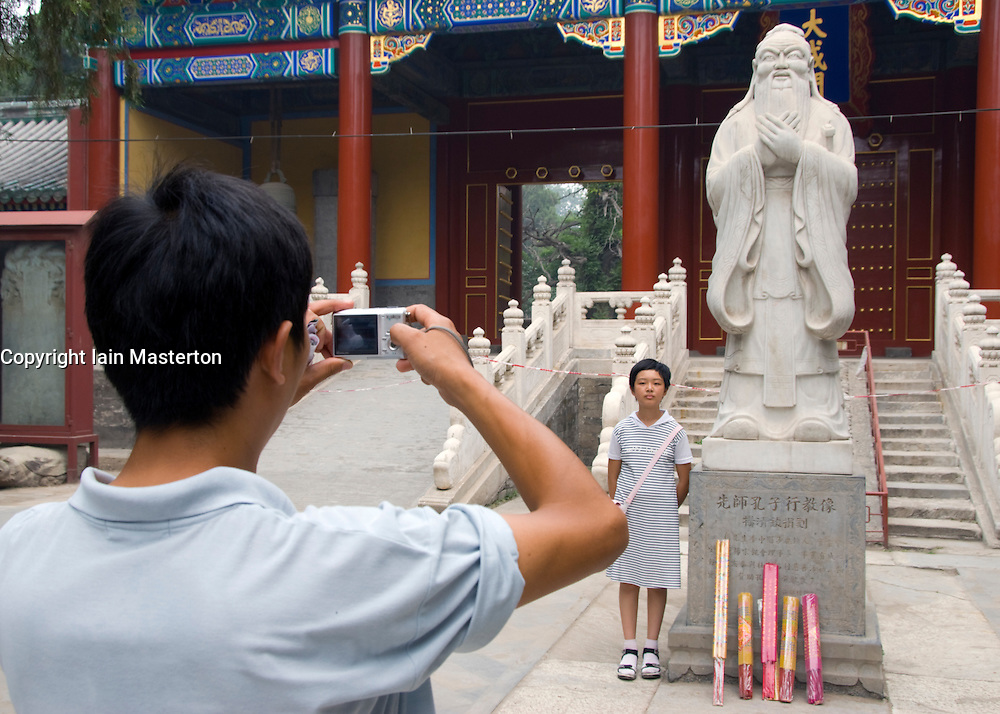 Father photographs daughter beside statue of Confucius at Confucian Shrine in Beijing