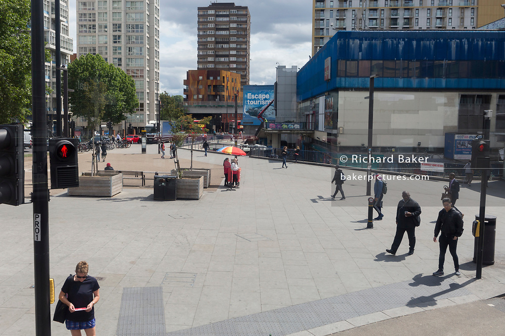 Pedestrians and a multi-coloured umbrella at Elephant & Castle in Southwark, on 5th June 2019, in London, England.