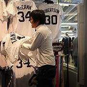 Japanese baseball fans in the Yankee Stadium shop buying shirts of Masahiro Tanaka on game day of Masahiro Tanaka, New York Yankees, pitching during the New York Yankees Vs Tampa Bay Rays, Major League Baseball game at Yankee Stadium, The Bronx, New York. 3rd May 2014. Photo Tim Clayton
