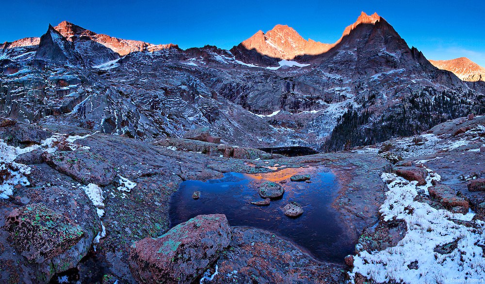 Black lake can be seen far below this frozen tarn in Rocky Mountain National Park. The sharp peak to the left is The Spearhead. McHenrys Peak and The Arrowhead are at right. A six-mile nocturnal hike was required to arrive at this location before sunrise.