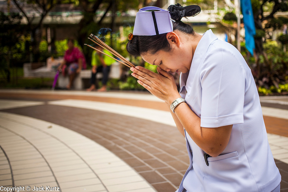 26 NOVEMBER 2012 - BANGKOK, THAILAND:   A nurse prays for the hospitalized King in the courtyard at Siriraj Hospital, outside the wing housing the King of Thailand, in Bangkok. Siriraj was the first hospital in Thailand and was founded by King Chulalongkorn in 1888. It is named after the king's 18-month old son, Prince Siriraj Kakuttaphan, who had died from dysentery a year before the opening of the hospital. It's reported to one of the best hospitals in Thailand and has been home to Bhumibol Adulyadej, the King of Thailand, since 2009, when he was hospitalized to treat several ailments. Since his hospitalization tens of thousands of people have come to pay respects and offer get well wishes. The King's 85th birthday is on Dec 5 and crowds at the hospital are growing as his birthday approaches. The King is much revered throughout Thailand and is seen as unifying force in the politically fractured country.      PHOTO BY JACK KURTZ