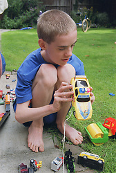 Teenage boy with autism crouching down outside in garden playing with remote controlled toy car,