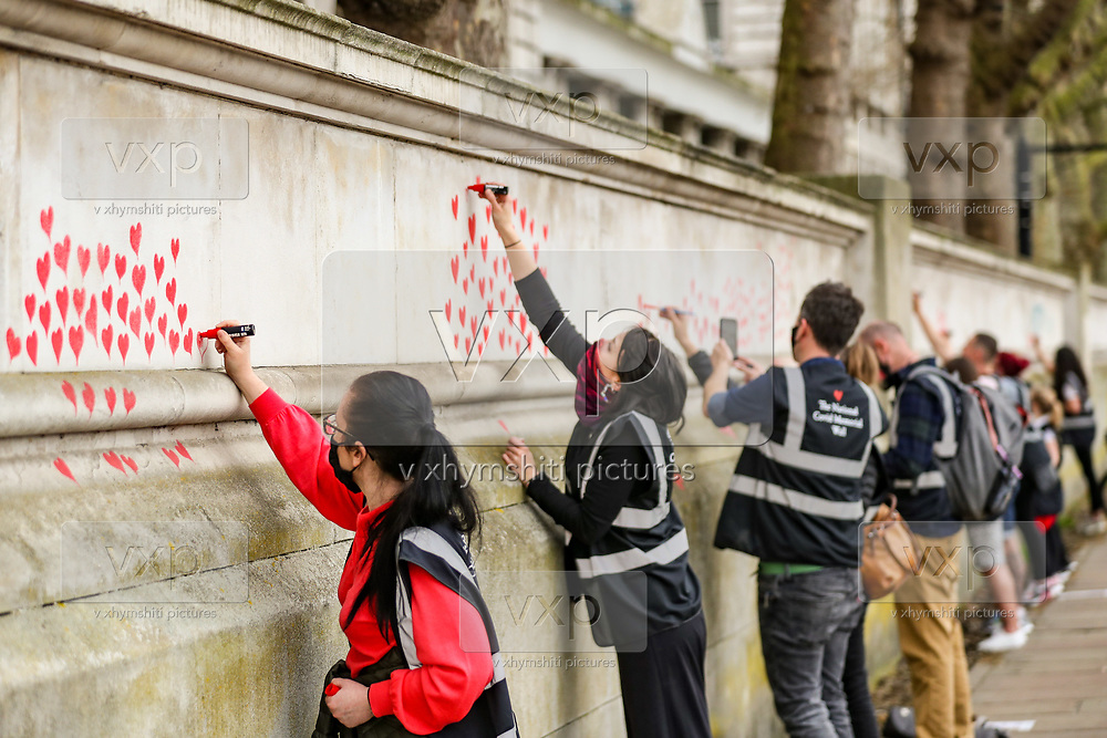 Red hearts are seen on the National Covid Memorial Wall in London just opposite Westminster Palace by St Thomas' Hospital on Wednesday, March 31, 2021. Nearly 150,000 hearts will be painted by volunteers and relatives of the bereaved along a wall beside St Thomas' hospital as a memorial to all those who have died so far in the UK from COVID-19, amid the spread of the coronavirus disease pandemic in Britain. (Photo/ Vudi Xhymshiti)