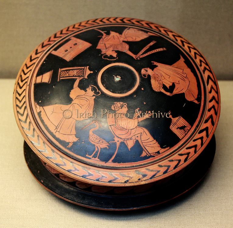 Greek 'pyxis' or trinket-box adorned with red figures. Showing a woman holding a 'sprang' frame. Made in Athens around 470 BC.