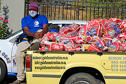 JOHANNESBURG, SOUTH AFRICA - MAY 08: A volunteer with food parcels outside Celebration Church  on May 08, 2020 in Diepsloot, South Africa. In partnership with with government and Celebration Church, Engen Fuel Retailers contributed food parcels for over 4000 familes in Diepsloot during lockdown level 4. (Photo by Dino Lloyd)
