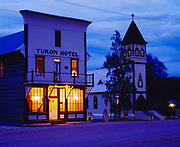 Yukon Hotel, two story log building with facade of milled lumber built in 1898, and Saint Paul's Anglican-Episcopalian Church built in 1902, Klondike Gold Rush town of Dawson City, Yukon Territory, Canada.