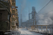 A view of an abandoned workers housing complex as water vapor and smoke rise from a Tonghua Iron & Steel Group Co. plant in the distance in the Erdaojiang district in Tonghua, Jilin province, China, on Wednesday, Jan. 6, 2016. The citys once-vaunted state-run steel mills have slipped inexorably into decline, weighed down by slumping global markets, a changing economy, and the burden of costs and responsibilities to the people of the town they fostered. Previous attempts to privatise the enterprise have met with stiff resistance, one such attempt resulted the mob lynching and death of a private businessman who wanted to invest and streamline the operation.