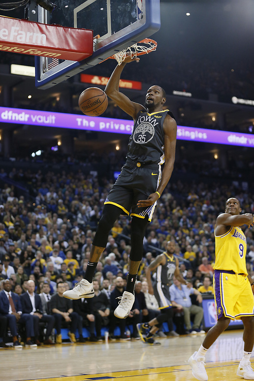 Golden State Warriors forward Kevin Durant (35) dunks as Los Angeles Lakers guard Rajon Rondo (9) watches in the first half of an NBA game at Oracle Arena on Saturday, Feb. 2, 2019, in Oakland, Calif.