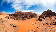 Tourists hike up a red sand dune from their Jeep in Wadi Rum, Jordan.
