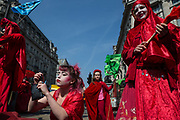 A woman in a red costume applies make-up during a protest against climate change in the middle of Oxford Circus on 15th April, 2019 in London, United Kingdom.  Extinction Rebellion have blocked five central London landmarks in protest against government inaction on climate change. .