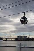 An Emirates Air Line Cable Car takes passengers across the River Thames between Greenwich Peninsula and the Royal Docks in London, England, United Kingdom. The Royal Victoria Bridge can be seen in the background.