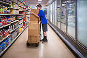 "08 JULY 2020 - JEWELL, IOWA: TREVOR ZANKER breaks down boxes in the frozen food aisle at Jewell Market. The only grocery store in Jewell, a small community in central Iowa, closed in 2019. It served four communities within a 20 mile radius of Jewell. Some of the town's residents created a cooperative to reopen the store. They sold shares to the co-op and  held fundraisers through the spring. Organizers raised about $225,000 and bought the store, which reopened July 8. Before the reopening, Jewell had been a ""food desert"" for seven months. The USDA defines rural food deserts as having at least 500 people in a census tract living 10 miles from a large grocery store or supermarket. There is a convenience store in Jewell, but it sells mostly heavily processed, unhealthy snack foods that are high in fat, sugar, and salt.        PHOTO BY JACK KURTZ"