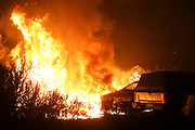 The Blue Cut wildfire burns the vehicles near Cajon Pass, north of San Bernardino, Calif., August 16, 2016. The fire is currently 9,000 plus acres, with 700 personnel on scene. Fifty-seven engines, 8 crews, 8 air tankers, 2 Very Large Air Tankers (VLATS), with additional firefighters and equipment on order. There is imminent threat to public safety, rail traffic and structures. With this being a very quickly growing wildfire, evacuation instructions have been issued. An estimated 34,500 homes and 82,640 people are being affected by the evacuation warnings.  AFP PHOTO / Ringo Chiu