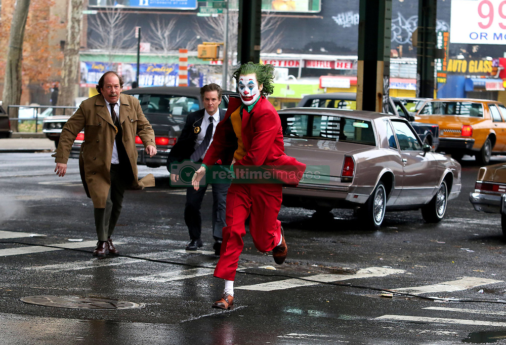 """Joaquin Phoenix in full joker costume and make-up is seen running at full speed while filming an intense scene where he is being pursued by costars Shea Whigham and Bill Camp who will be playing two Gotham Police Detectives for the upcoming JOKER movie. The scene involved a dangerous stunt where Joaquin's Stunt Double took a nasty hit by a taxi while filming under an elevated train station in the Bronx. Later in the day Joaquin was off his Joker costume and shot some gritty looking scenes as his other character known as """"Arthur Fleck"""". 18 Nov 2018 Pictured: Joaquin Phoenix. Photo credit: LRNYC / MEGA TheMegaAgency.com +1 888 505 6342"""