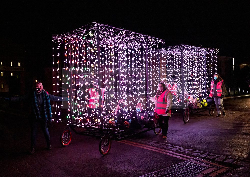 © Licensed to London News Pictures; 10/12/2020; Gloucester, UK. 'Travelling Light' has its world premiere at the first edition of Bright Nights, a collection of light installations by local and international artists which will illuminate the streets of Gloucester as the nights get longer over winter. Travelling Light is a new mobile artwork by the digital art group Squidsoup, inspired by travelling funfairs, circuses and carnivals and bringing light and sound to the heart of Gloucester to spread joy during during the Covid-19 coronavirus pandemic in England. Moving through the streets thousands of points of lights mounted onto bicycles dance and pulse to a soundtrack created by Dylan Williams. It will travel the streets of Gloucester for three nights in the run up to Christmas. Photo credit: Simon Chapman/LNP.