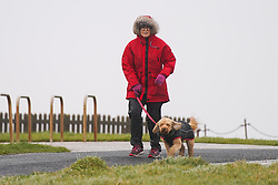 © Licensed to London News Pictures. 28/03/2021. Blackpool, UK. A dog walker walks along the promenade as she battles the high winds in Blackpool this afternoon.Photo credit:  Ioannis Alexopoulos/LNP