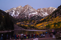 Photographers line up along the shore of Maroon Lake to photograph Maroon Bells at sunrise.  Elk Mountains, Colorado.