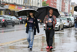 © Licensed to London News Pictures. 04/06/2021. London, UK. A couple shelter from the rain beneath umbrellas during rainfall in north London. According to The Met Office, more rain is expected today across London and the South East of England, with the hot weather returning tomorrow. Photo credit: Dinendra Haria/LNP