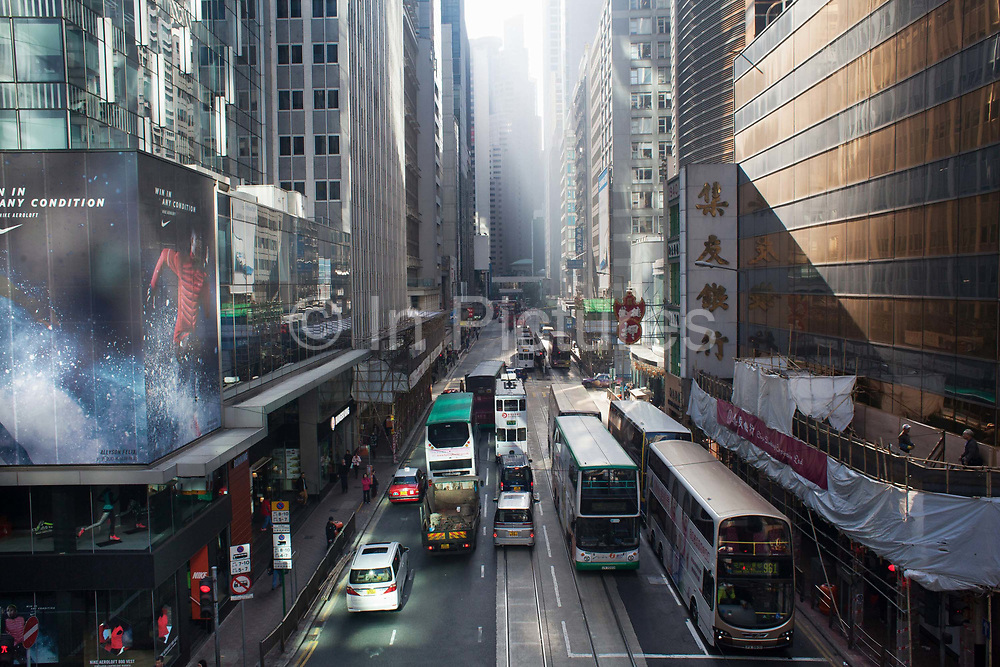 Des Voeux Road and traffic in morning sun in Central district. Busses, trams and cars. 7 million people live on 1,104km square, making it Hong Kong the most vertical city in the world.