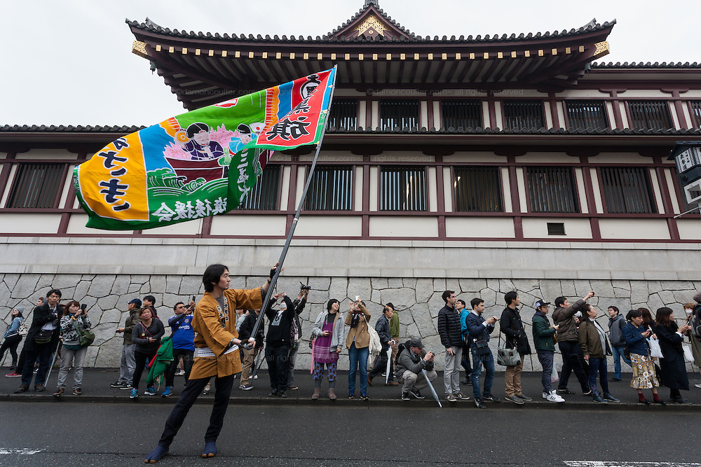 Festival supporters carry and wave a huge flag during the Kanamara Matsuri, (Festival of the Steel Phallus). Kawasaki Daishi, Kanagawa, Japan. Sunday April 3rd 2016. The famous Kawasaki Penis Festival started in 1977 as a small festival to celebrate an old legend about the defeat of a penis eating demon. Today the festival is a huge draw for Japanese and foreign tourists and raises money for HIV and AIDS research.