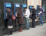 Line of five people at cash point machines, London, England