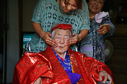 Ayumi Naka massages the face of her grandmother, 97-year-old Tomi Miyagi, to prepare for a celebration in her honor at the town hall in Ogimi, Okinawa.