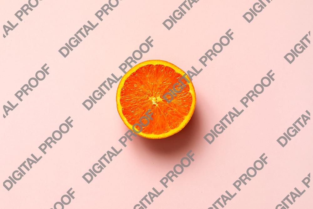 Orange fruit. Orange half fruit sliced isolate on pink background seen from above flatlay style, close up.
