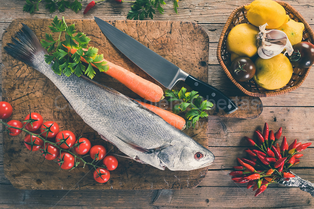 Shi drum fish (Umbrina cirrosa) on old wooden board with carrot, cherry tomatoes, black tomatoes, lemon, garlic, parsley and chili peppers, top view shot.