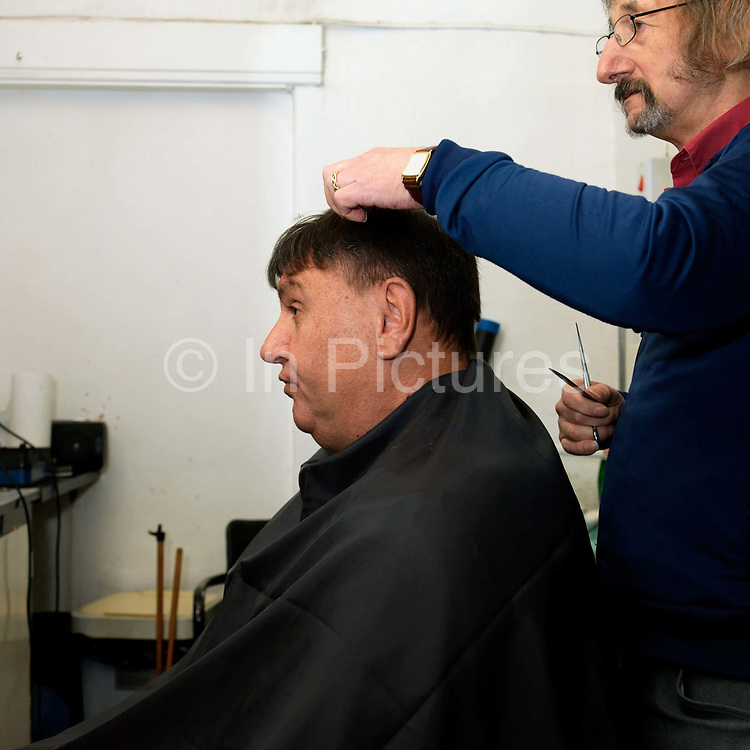 Barber Paul Youle cutting a customers hair at his barber's shop 'Stallions', Parson Cross, Sheffield, South Yorkshire, UK