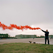 Engineering ground staff member of the Red Arrows, Britain's RAF aerobatic team, tests red smoke canister in a regular safety procedure. The man belongs to a team of highly-skilled engineers known as the  'Blues' who support the pilots known as the Reds. Eleven trades skills are imported from some sixty that the Royal Air Force (RAF) employs and teaches. The better-educated officers in the armed forces enjoy a more privileged lifestyle than their support staff. In the aerobatic squadron, the Blues outnumber the pilots 8:1. Without them, the Red Arrows couldn't fly.