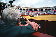 """Old man watching the bullfighting. Bullfighting in Sevilla's famous bullring """"La Real Maestranza"""" is a significant part of the Feria de Abril..The Feria de abril de Sevilla, """"Seville April Fair"""" dates back to 1847. During the 1920s, the feria reached its peak and became the spectacle that it is today. It is held in the Andalusian capital of Seville in Spain. The fair generally begins two weeks after the Semana Santa, Easter Holy Week. The fair officially begins at midnight on Monday, and runs six days, ending on the following Sunday. Each day the fiesta begins with the parade of carriages and riders, at midday, carrying Seville's citizens to the bullring, La Real Maestranza...For the duration of the fair, the fairgrounds and a vast area on the far bank of the Guadalquivir River are covered in rows of casetas (individual decorated marquee tents which are temporarily built on the fairground). Some of these casetas belong to the prominent families of Seville, some to groups of friends, clubs, trade associations or political parties. From around nine at night until six or seven the following morning, at first in the streets and later only within each caseta, crowds of people party and dance Sevillanas, traditional Flamenco dances, Sevillan style drinking Jerez sherry, or Manzanilla wine, and eating tapas. .."""