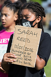 Slough, UK. 13 June, 2020. A young girl holds a sign bearing the name of Sarah Reed, who was found dead in her cell at Holloway prison in 2016, during a peaceful protest in solidarity with the Black Lives Matter movement on 13th June 2020 in Salt Hill Park in Slough, United Kingdom. Protests in solidarity with the Black Lives Matter movement have taken place across the United States and in many countries around the world.