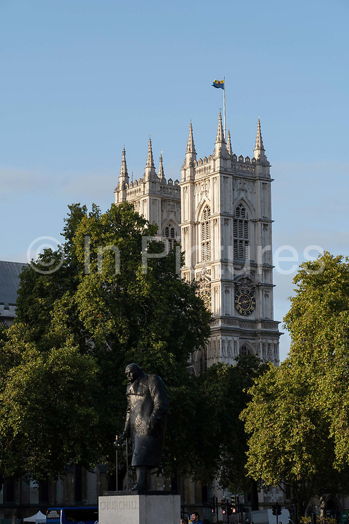 Westminster Abbey with the Winston Churchill statue in the foreground on the 4th October 2019 in London in the United Kingdom. Westminster Abbey, formally titled the Collegiate Church of Saint Peter at Westminster, is a large, mainly Gothic abbey church in the City of Westminster, London, England.