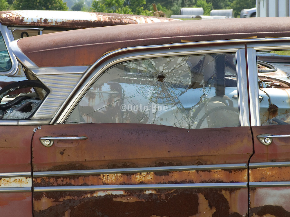 side view of old rusted junkyard car with window with a large bullet hole