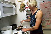 Christian, 35, dumpster diving since more than eight years is cookins some mushrooms in the kitchen at a Freegan dinner made entirely with food recovered from dumping sites around the island of Manhattan, New York, NY., on Friday, June 23, 2006. Freegans are a community of people who aims at recovering wasted food, books, clothing, office supplies and other items from the refuse of retail stores, frequently discarded in brand new condition. They recover goods not for profit, but to serve their own immediate needs and to share freely with others. According to a study by a USDA-commissioned study by Dr. Timothy Jones at the University of Arizona, half of all food in the United States is wasted at a cost of $100 billion dollars every year. Yet 4.4 million people in the United States alone are classified by the USDA as hungry. Global estimates place the annual rate of starvation deaths at well over 8 million. The massive waste generated in the process fills landfills and consumes land as new landfills are built. This waste stream also pollutes the environment, damages public health as landfills chemicals leak into the ground, and incinerators spew heavy metals back into the atmosphere. Freegans practice strategies for everyday living based on sharing resources, minimizing the detrimental impact of our consumption, and reducing and recovering waste and independence from the profit-driven economy. They are dismayed by the social and ecological costs of an economic model where only profit is valued, at the expense of the environment. In a society that worships competition and self-interest, Freegans advocate living ethical, free, and happy lives centred around community and the notion that a healthy society must function on interdependence. Freegans also believe that people have a right and responsibility to take back control of their time.