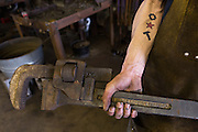Blacksmiths hands on a giant wrench in a metal working shop in Charleston, SC
