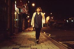 Teenage girl walking along street at night,