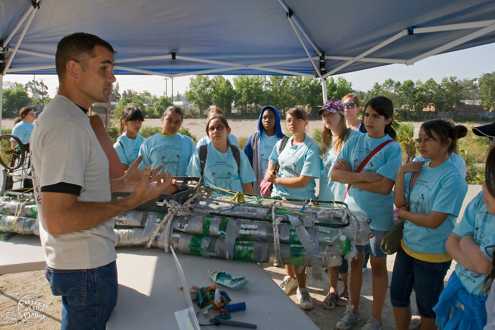 Marcus Eriksen of Algalita Marine Research Foundation talks to school children about the plastic bottle kayak that Marcus is displaying at the FoLAR (Friends of the LA River) clean-up at the Glendale Narrows. Los Angeles, California, USA
