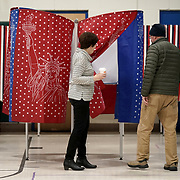 An election official helps a voter cast their ballot in the presidential primary at the Parker-Varney School in Manchester, N.H., on Tuesday, February 11, 2020.