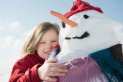 Girl with snowman, smiling, Bavaria, Germany