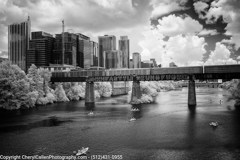 View of the Austin, Texas skyline from Lady Bird lake with passing train and Stand up paddle boarders in Infrared