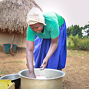 CAPTION: Catherine washes the dishes, following a meal. She used to have multiple sexual partners, something that made her vulnerable to HIV/AIDS. That was until the intervention of a program run by World Renew's partner, the Kaberamaido Mission Development Program. She now makes sure that her only partner is her husband David, who is himself a health champion in the area. LOCATION: Apapai Parish, Otuboi Sub-county, Kalaki County, Kaberamaido District, Uganda. INDIVIDUAL(S) PHOTOGRAPHED: Catherine Anaso.