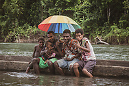 Residents of the village of Likan, located in East Sepik Province in Papua New Guinea, pose for a picture on the edge of a dugout canoe on the Clay River.  (June 21, 2019)