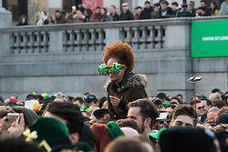 London, March 13th 2016. The annual St Patrick's Day Festival takes place in Trafalgar Square with performances on stage and plenty of Irish food and drink for the thousands of revellers.  PICTURED: A woman wears clover leaf glasses as she sits on someone's shoulders to enjoy the performance on stage.. ©Paul Davey<br /> FOR LICENCING CONTACT: Paul Davey +44 (0) 7966 016 296 paul@pauldaveycreative.co.uk