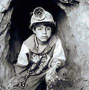 Portrait of a child miner holding bag of cocoa leaves at the Potosi Mine, Potosi, Eastern Cordillera, Bolivia